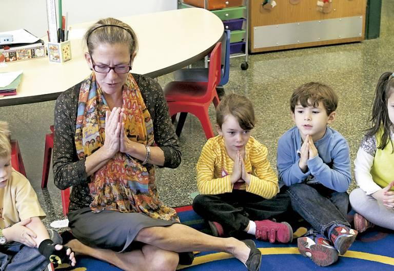 niños pequeños en el aula con la profesora rezando