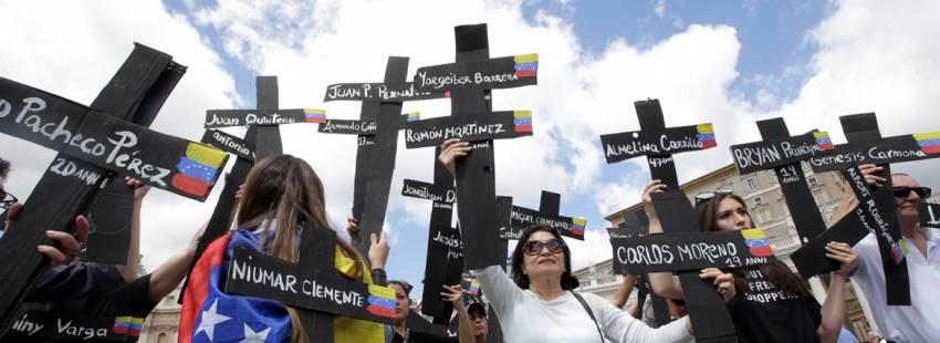 peregrinos de Venezuela en el Vaticano con cruces con nombres de víctimas de la crisis
