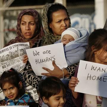 madres y niños refugiados en Grecia protesta con carteles Somos humanos demandan mejores condiciones de vida campo refugiados