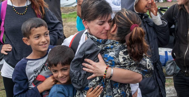 Una voluntaria a un grupo de refugiados en Grecia/CNS