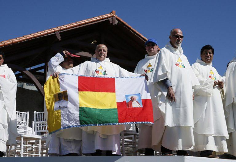 sacerdotes en Bolivia con bandera de Bolivia durante la visita del papa Francisco septiembre 2015