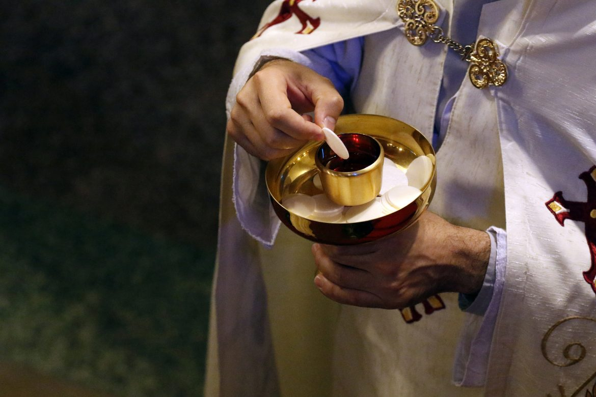 A priest prepares to distribute Communion during a Divine Liturgy June 26 at Our Lady of Lebanon Maronite Cathedral in Brooklyn, N.Y. Lebanese Cardinal Bechara Rai, patriarch of the Maronite Catholic Church, was the main celebrant of the liturgy. He arrived in the U.S. June 22 to begin a pastoral visit that concludes July 10. (CNS photo/Gregory A. Shemitz) See LEBANON-RAI June 28, 2016.