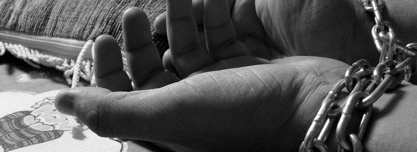 manos de mujer con cadenas trata de personas