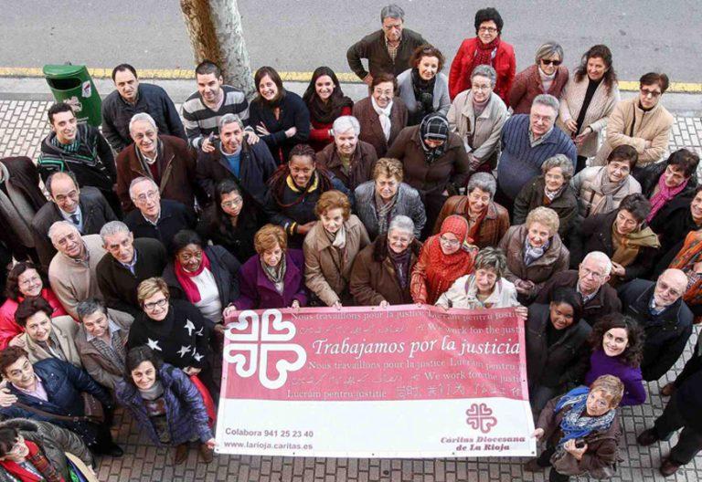 """Un grupo de voluntarios de Cáritas de La Rioja sostiene una pancarta con el lema """"Trabajamos por la justicia"""""""