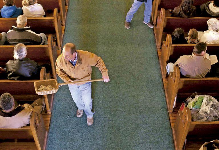 un hombre pasando el cepillo en una parroquia dinero iglesia