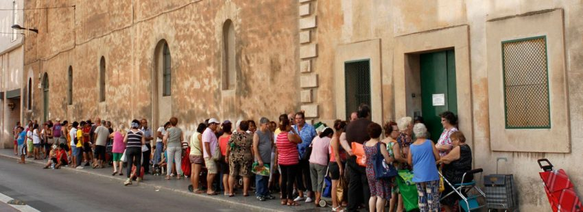 Un grupo de personas esperan para recibir alimentos Cáritas archivo