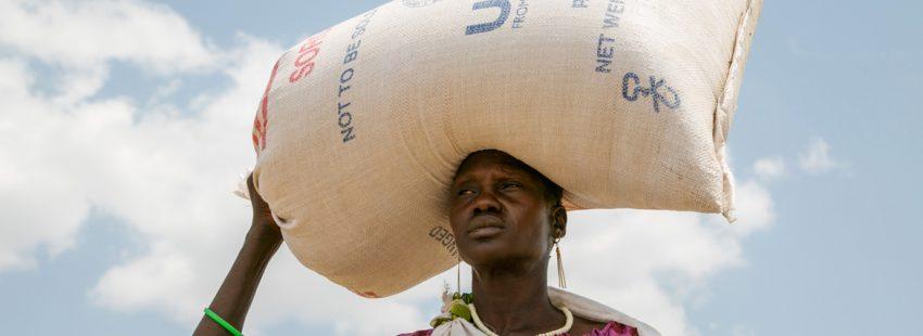 mujer en Sudán del Sur con un saco de comida ayuda humanitaria