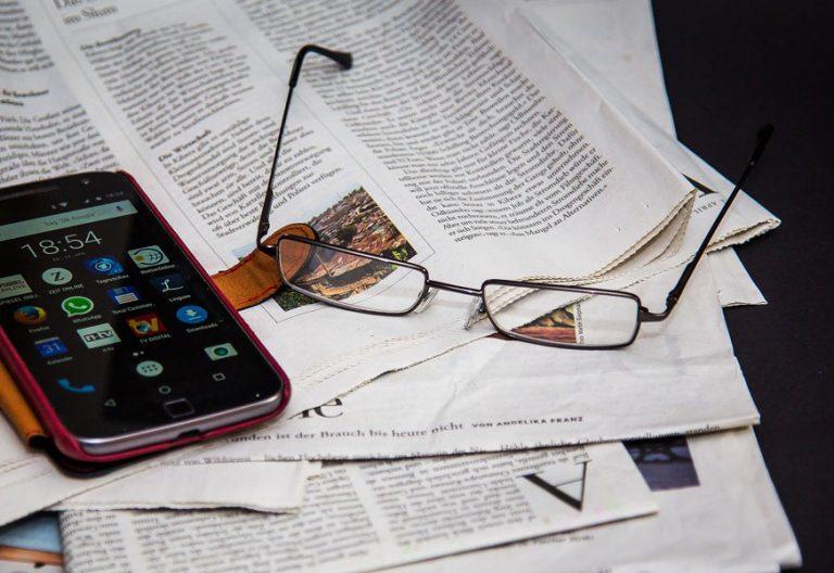 periódico en la mesa con unas gafas para leer y un teléfono móvil