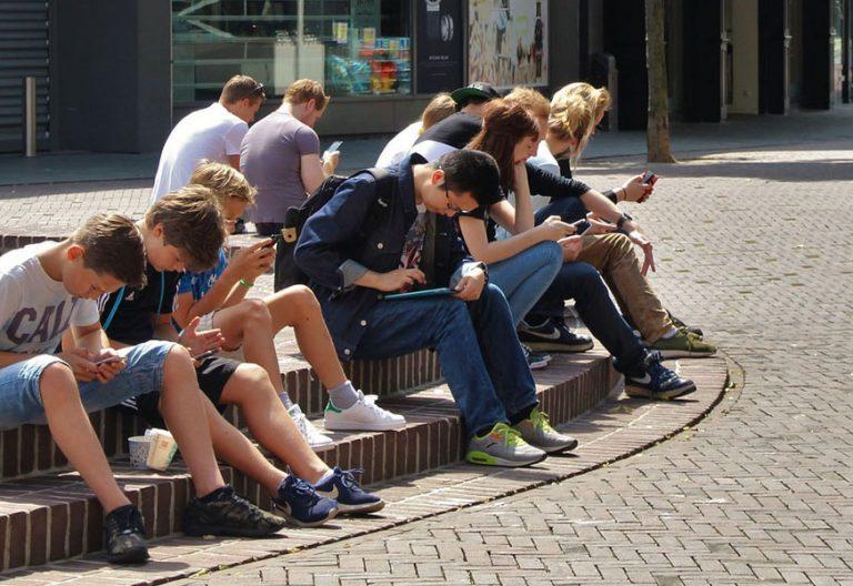grupo de jóvenes adolescentes en la calle estudiando sentados