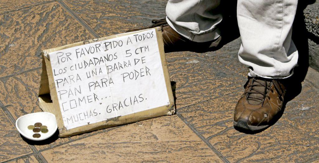 hombre pidiendo limosna en la calle con un cartel