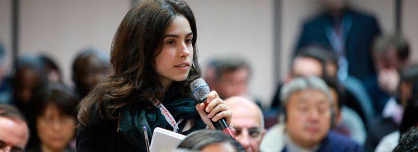 chica joven con micrófono en la mano habla en una asamblea eclesial