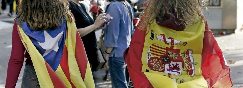 dos chicas con la bandera estelada independentistas de Cataluña y la bandera de España 1 octubre 2017