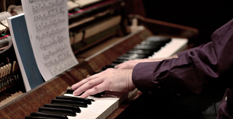 pianista manos de un músico tocando el piano con partitura