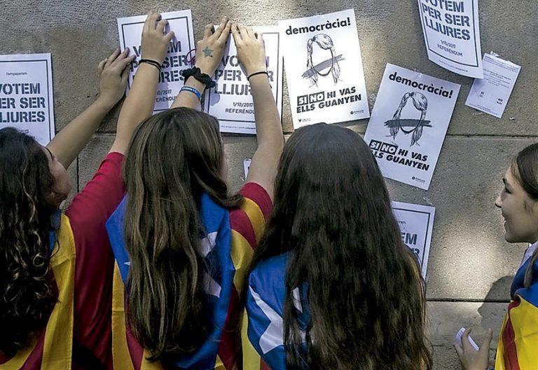 niñas jóvenes en Cataluña con bandera estelada independentista colgando carteles de propaganda