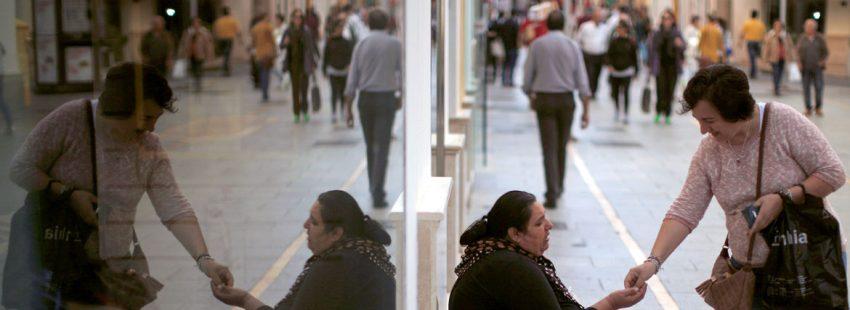 Una mujer le da dinero a otra que pide en la calle pobres