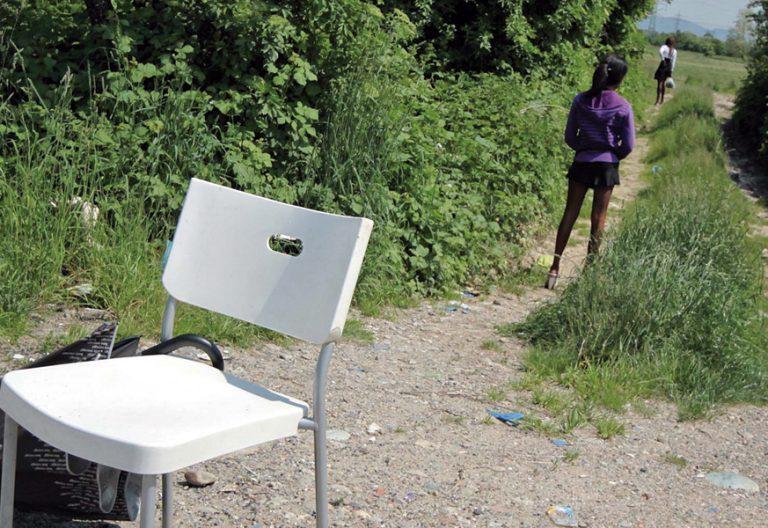 dos chicas jóvenes mujeres prostitulas en una selva o campo con una silla y un paraguas