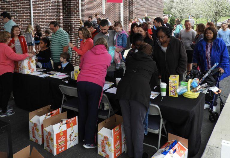 grupo de personas haciendo cola para recibir alimentos por parte de voluntarios