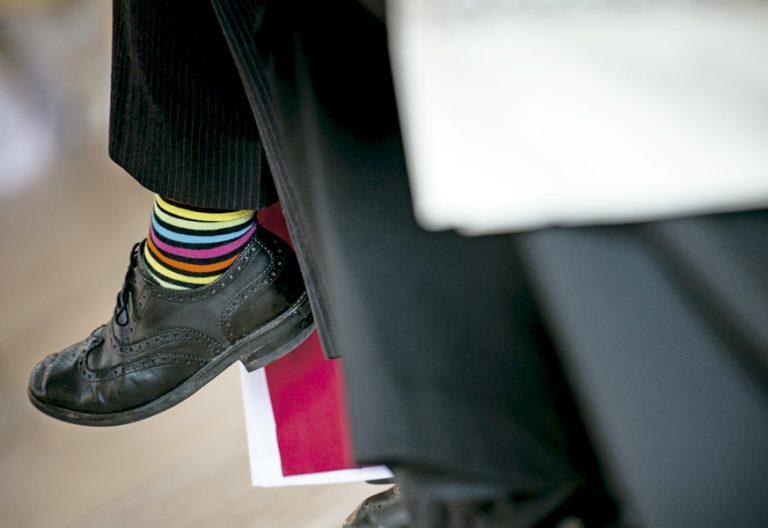 pierna de hombre con zapato negro y calcetín de varios colores