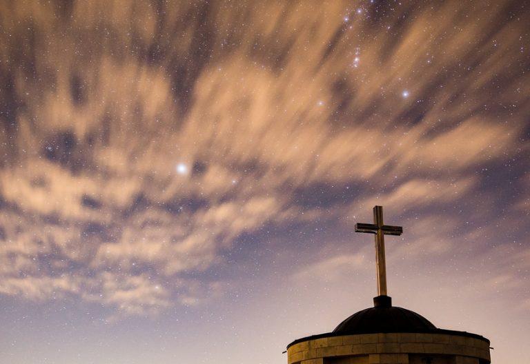 cruz cristiana en el horizonte de un cielo al atardecer