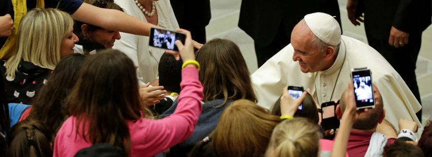papa Francisco con un grupo de jóvenes que les hacen fotos
