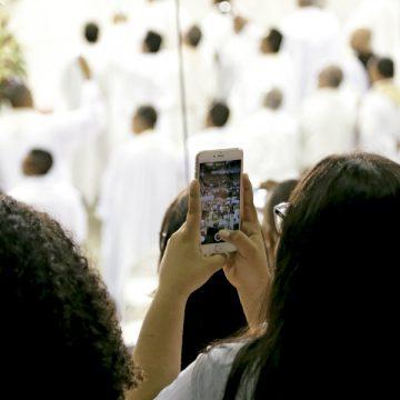jóvenes en misa haciendo una foto con el teléfono móvil