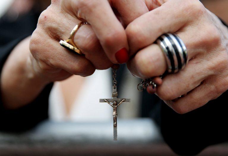 manos de mujer con un rosario rezando