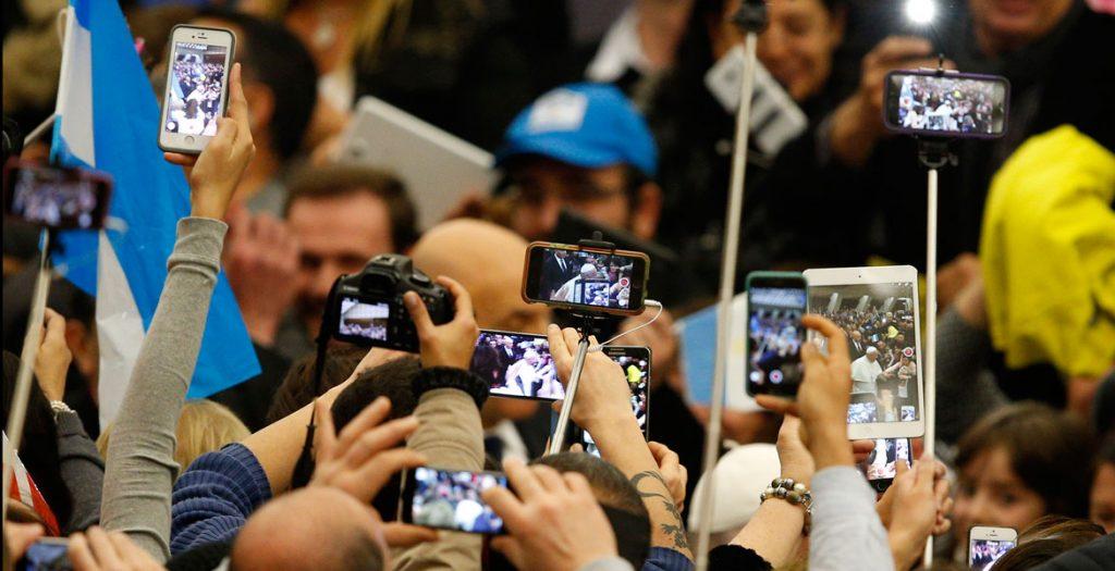 gente en una audiencia grabando con sus teléfonos al papa Francisco