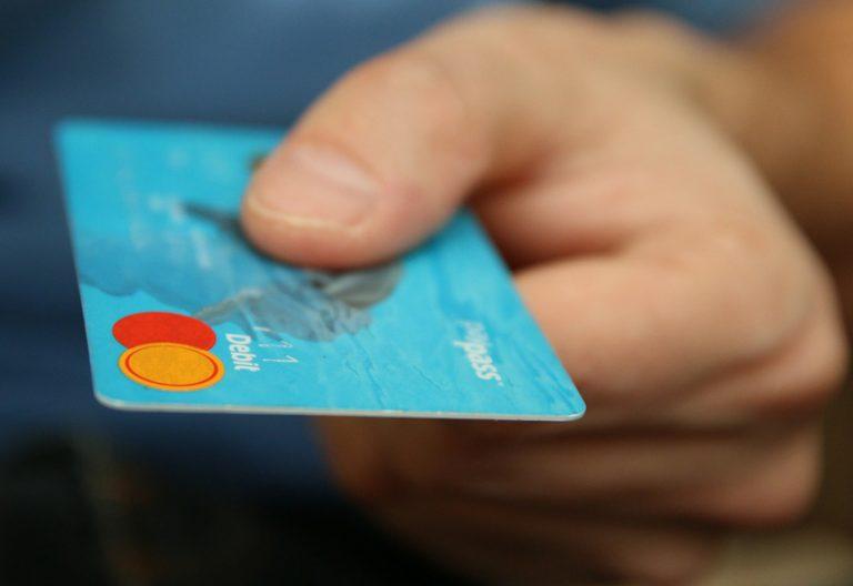 una mano sostiene una tarjeta de crédito para hacer una compra y pagar