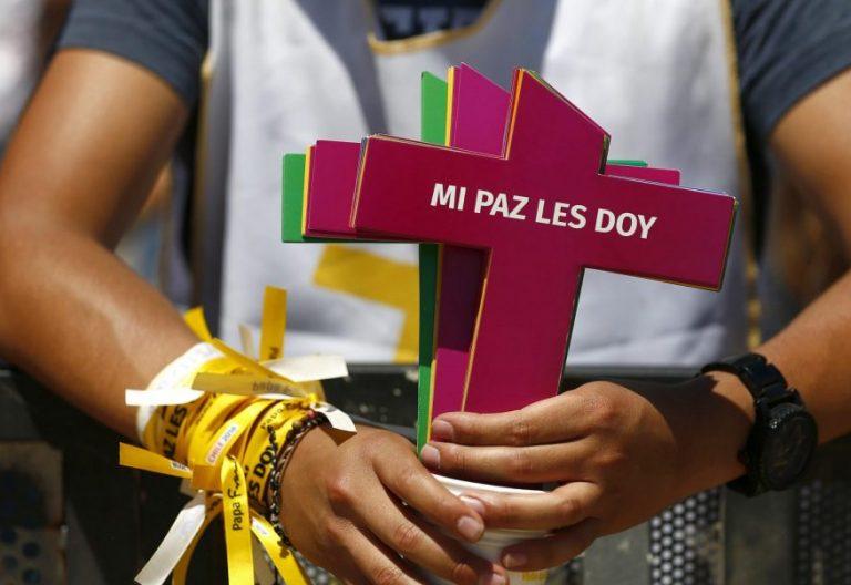 Un joven sujeta una cruz en Maipú, durante el viaje de Francisco a Chile/EFE
