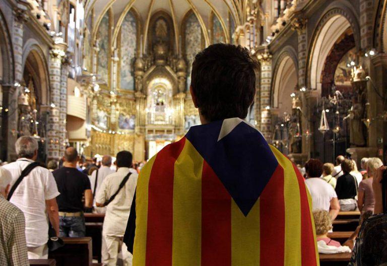 joven con una bandera estelada independentista Cataluña en una iglesia