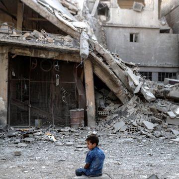 Un niño junto a una mezquita devastada por la guerra en Siria
