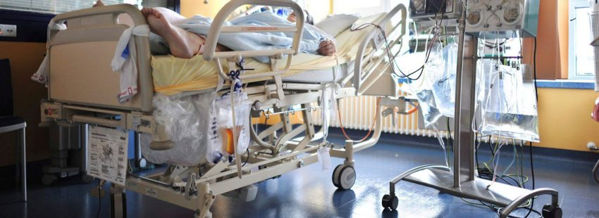 Un enfermo en una camilla en una habitación llena de aparatos médicos