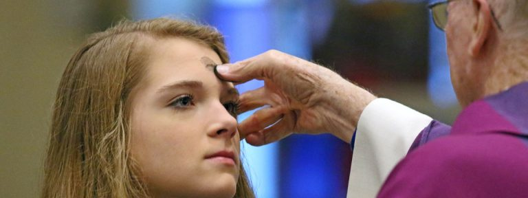 Una joven recibe la imposición de la ceniza en la la ceremonia que marca el inicio de la Cuaresma