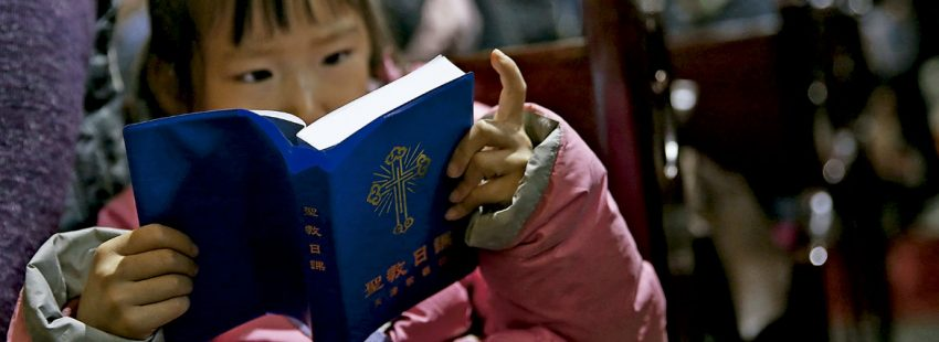 Una niña china, lee una biblia en misa