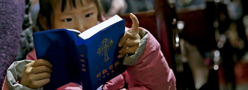 Una niña china, lee una biblia en misa