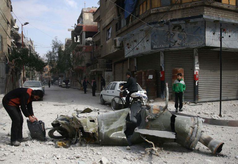 un hombre examina un misil en ghouta o guta, siria, periferia de damasco