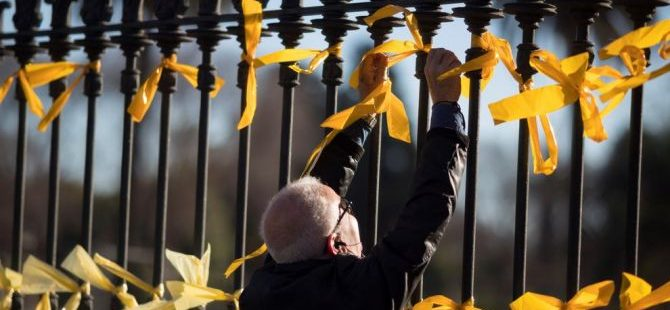 Un hombre coloca lazos amarillos para exigir la libertad de los presos del procés