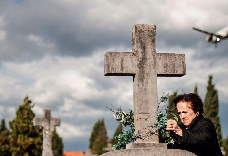 Mujer pone flores en un cementerio