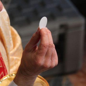 Un sacerdote dando la Comunion durante una Misa