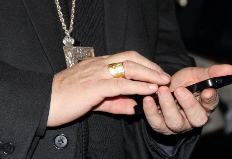 Un obispo manipula su teléfono móvil durante la Asamblea Plenaria de noviembre de 2014