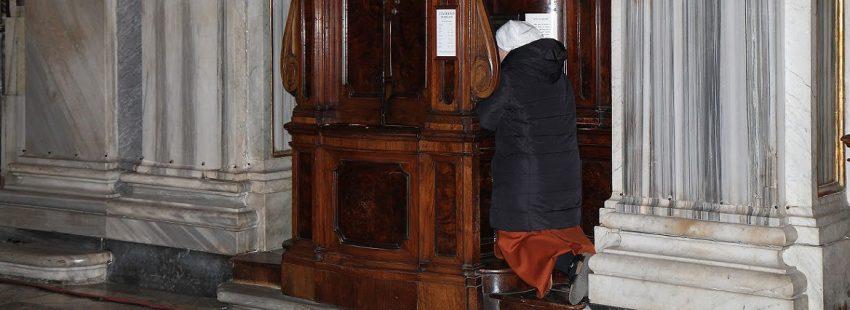 Una mujer se confiesa en una iglesia