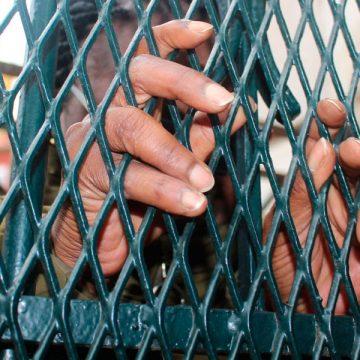 Víctima de trata posa ante unas rejas España Adoratrices Proyecto Esperanza