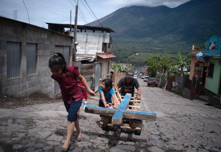Vecinos de Alotenango portan una cruz parara una de las víctimas del Volcán de Fuego en Guatemala