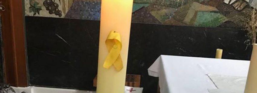 Lazo amarillo en un cirio del altar de la parroquia de comarruga