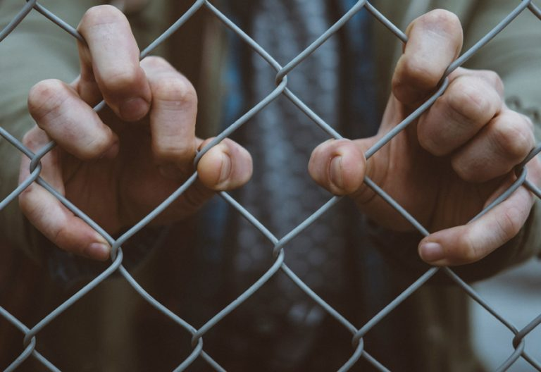 ua persona se agarra a una valla metalica encarcelada