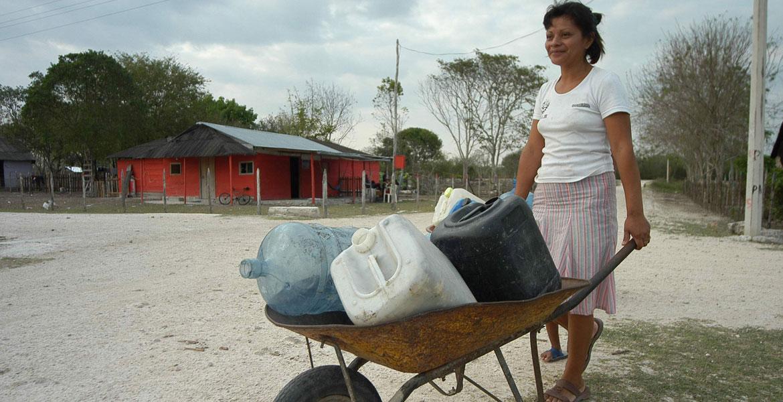 Una mujer acarrea bidones para surtirse de agua potable en una comunidad latinoamericana