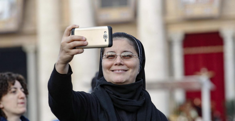 Una religiosa con un móvil, en la canonización de Oscar Romero/EFE
