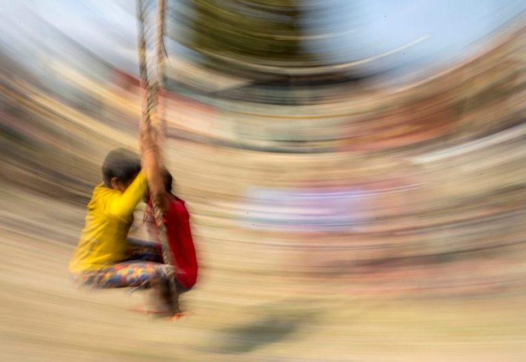 Niños jugando en un columpio/EFE
