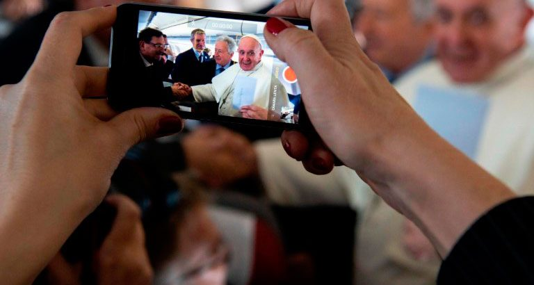 El corresponsal vaticano de Vida Nueva, Antonio Pelayo, saluda al papa Francisco en el vuelo con destino a Panamá