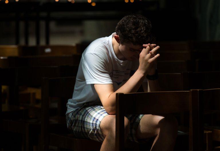 Un joven ora en una iglesia